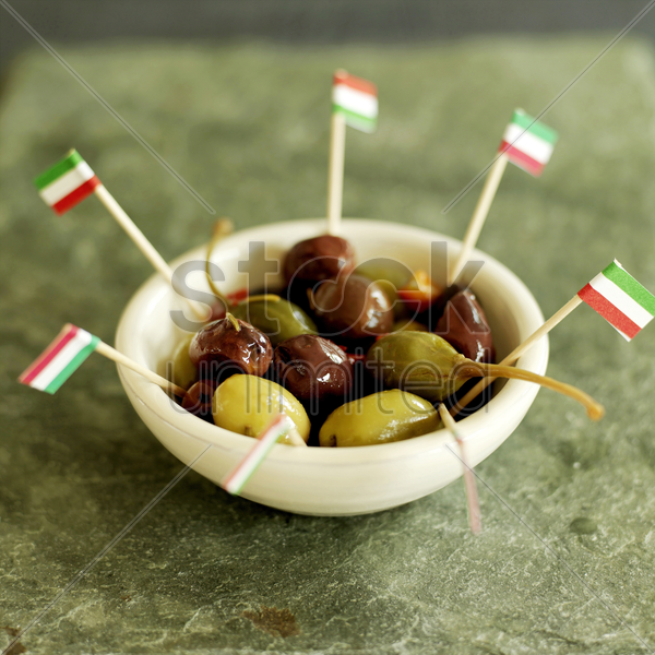 fresh italian olives in small ceramic bowl with italian flag picks stock photo