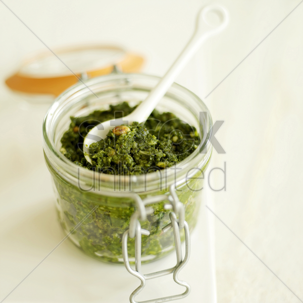 fresh italian pesto in a glass jar with a white ceramic spoon stock photo