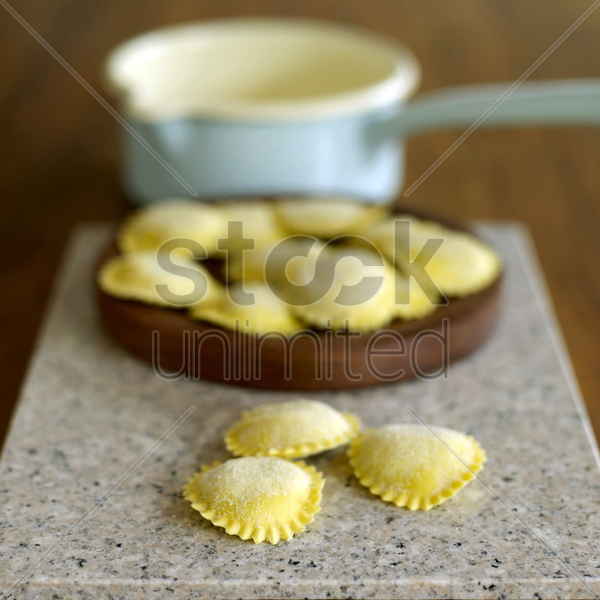 fresh tortellini pasta on wooden board stock photo