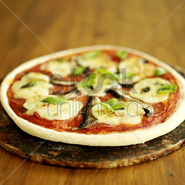 freshly cooked pizza sitting on a pizza stone stock photo
