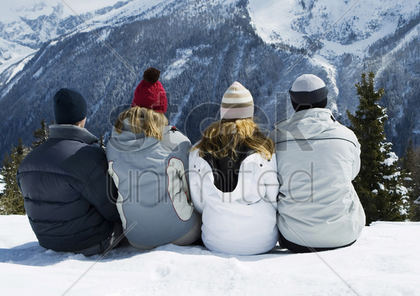friends sitting together, enjoying winter scenery stock photo