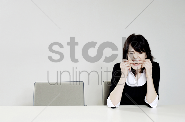 frustrated businesswoman biting a pencil stock photo