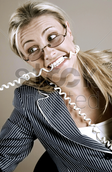 frustrated businesswoman biting the phone cord stock photo