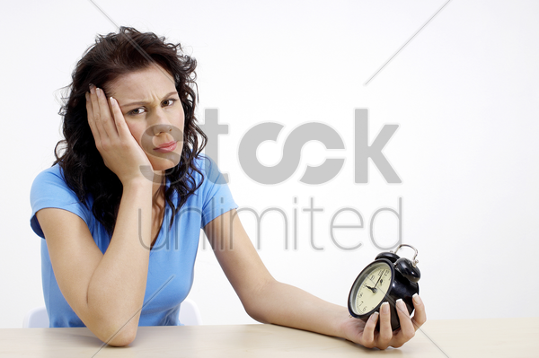 frustrated woman holding an alarm clock stock photo