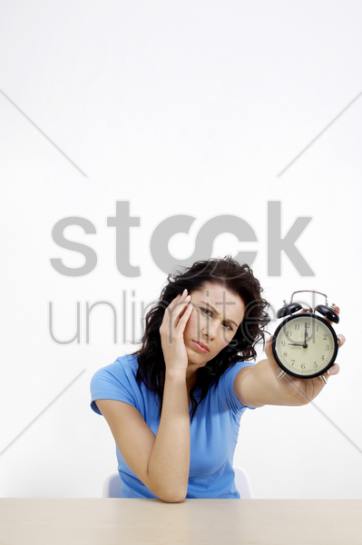 frustrated woman showing an alarm clock stock photo