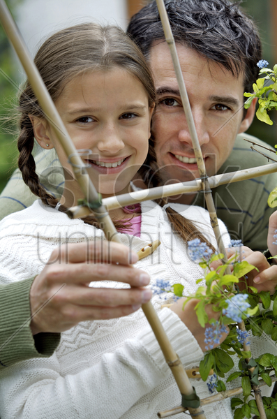 girl and man looking through wooden post with flowers stock photo