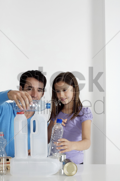 girl and man stacking empty bottles stock photo
