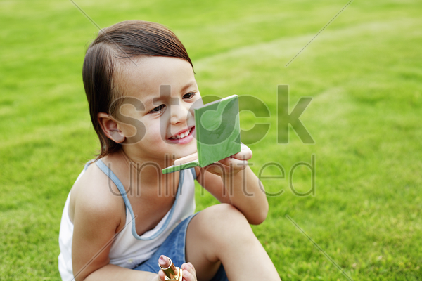 girl applying cosmetics on her face stock photo