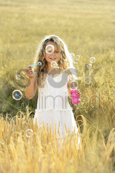girl blowing bubbles in the field stock photo