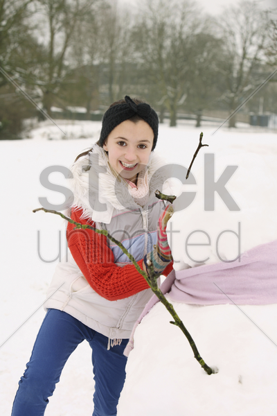 girl building snowman stock photo