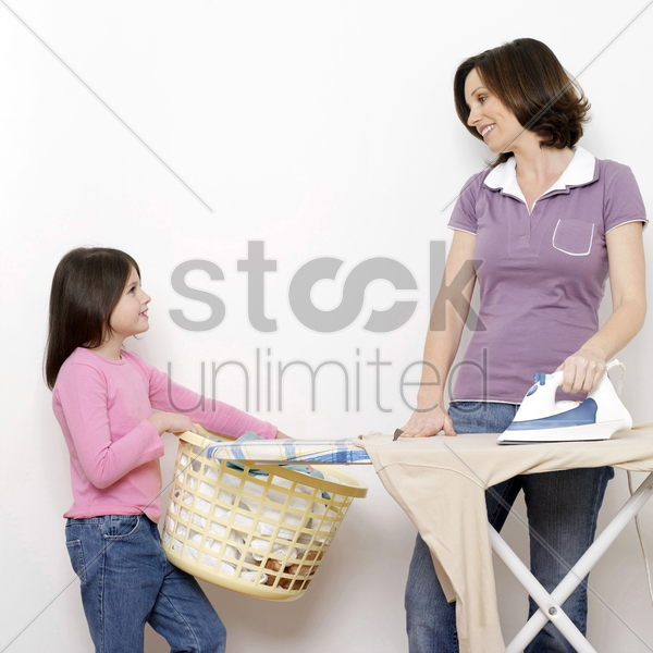 girl carrying a basket of clothes for her mother stock photo