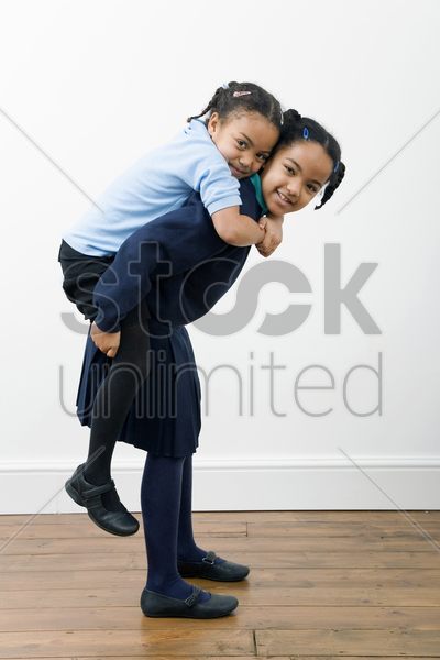 girl carrying her sister on her back stock photo