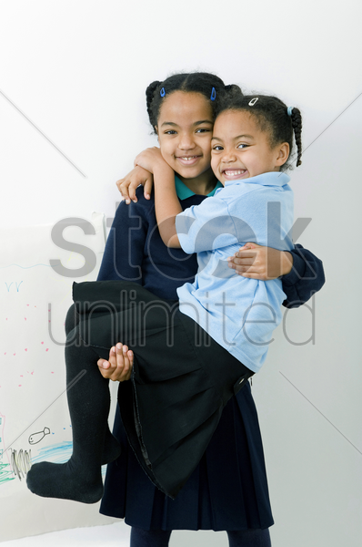 girl carrying her sister stock photo