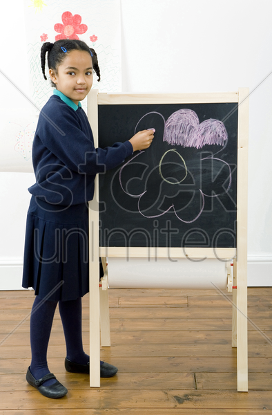 girl colouring a drawing on chalkboard stock photo