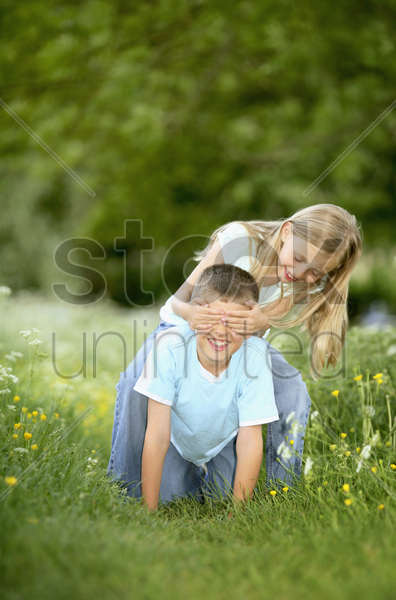 girl covering boy's eyes with her hands stock photo