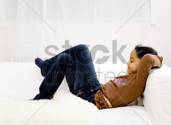 girl crossing her legs while resting on the couch stock photo