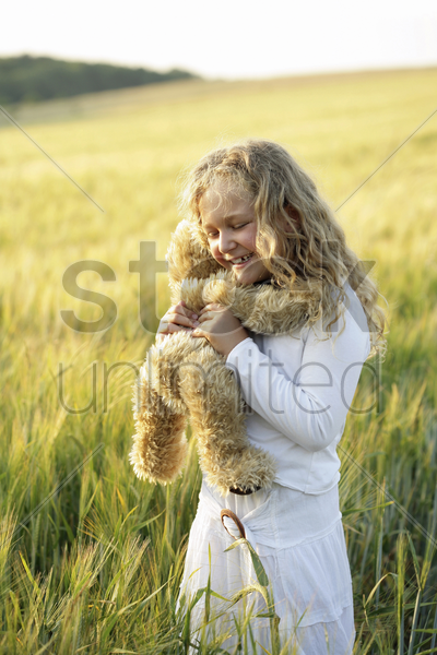 girl cuddling toy bear stock photo