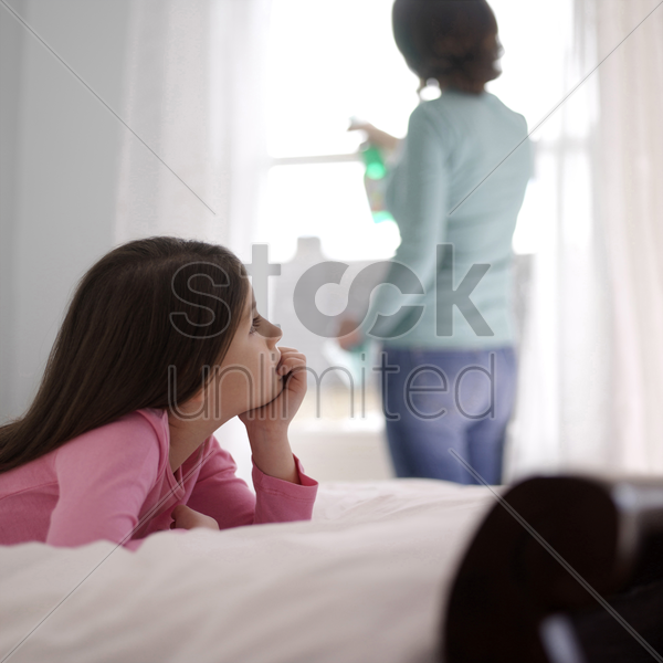 girl daydreaming on the bed while her mother is cleaning the window stock photo