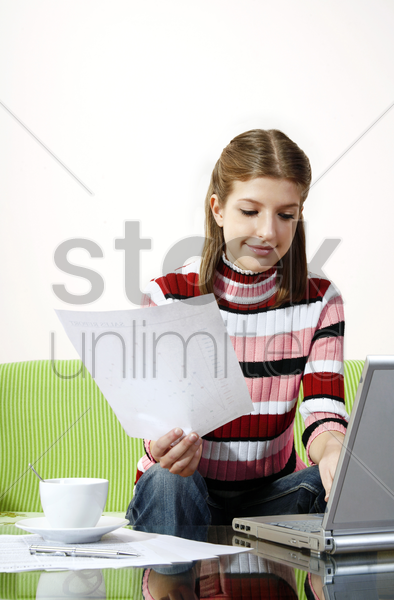 girl doing assignment on the laptop stock photo