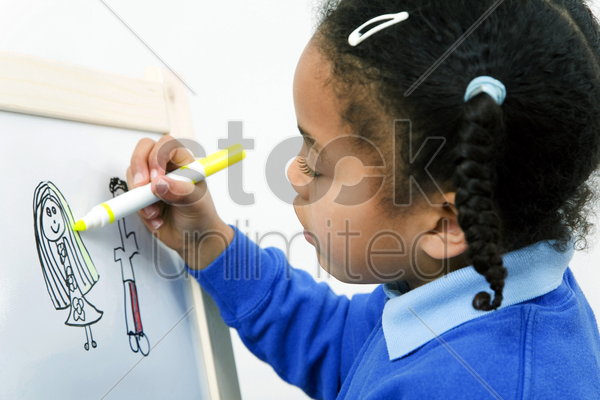 girl drawing picture on drawing board stock photo