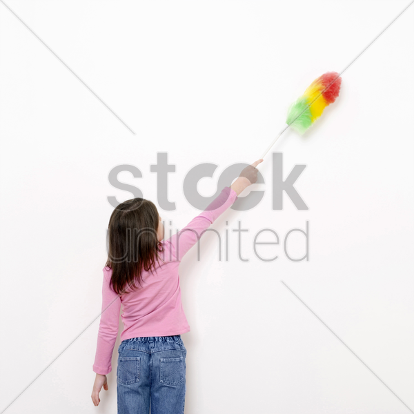 girl dusting the wall with a feather duster stock photo