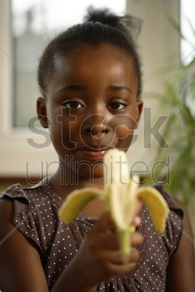 girl eating banana stock photo