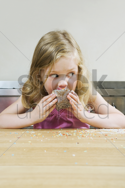 girl eating cupcake stock photo
