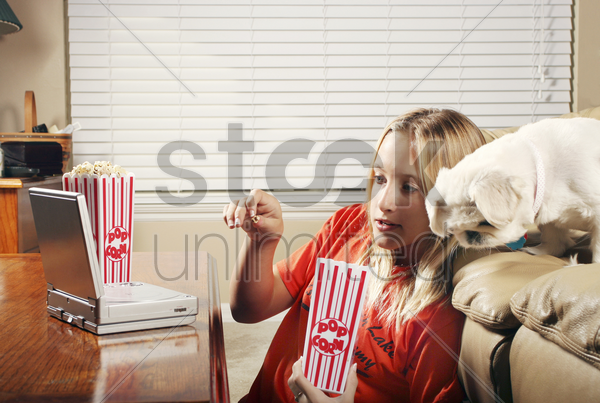 girl eating popcorn while watching movie on the portable dvd player stock photo