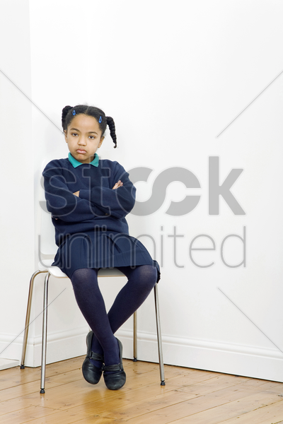 girl folding her arms while sitting on chair stock photo