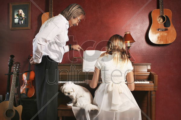 girl getting professional advice from her piano teacher stock photo