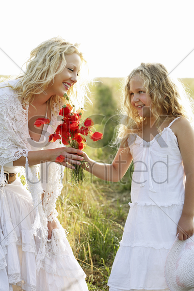 girl gives woman flowers stock photo
