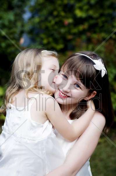 girl giving her sister a peck on the cheek stock photo