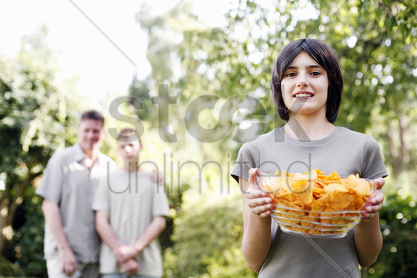 girl holding a bowl of potato chips stock photo