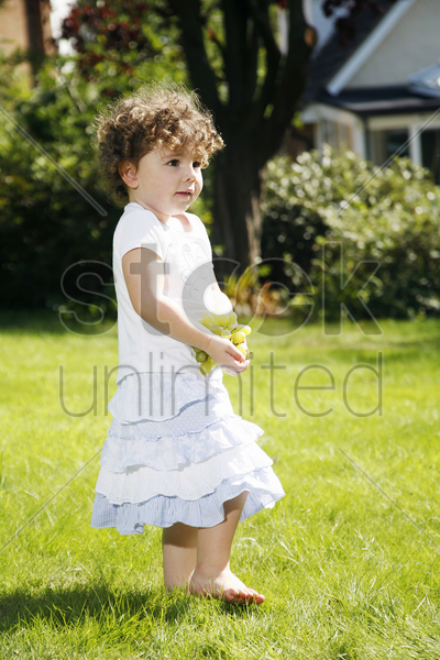 girl holding a bunch of green grapes while walking in the park stock photo