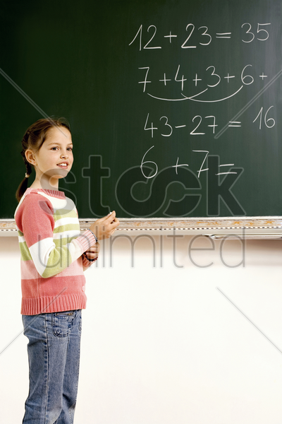 girl holding a chalk standing near the blackboard stock photo