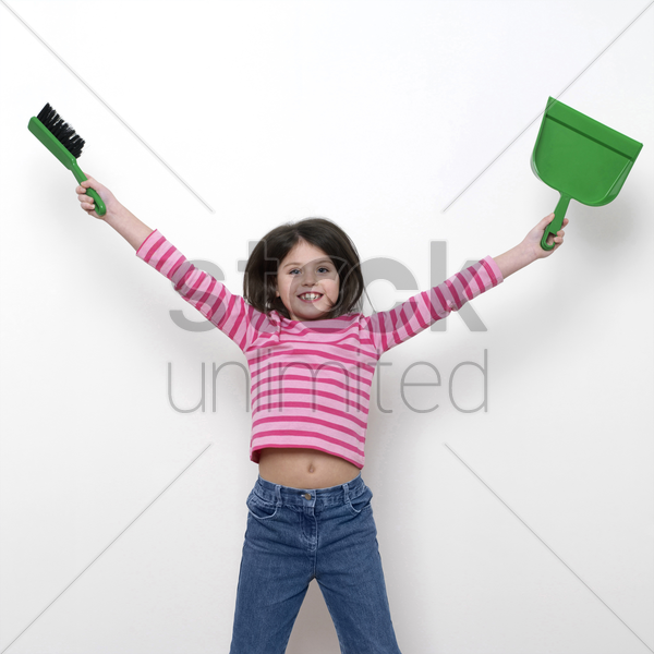 girl holding a dustpan and a brush stock photo