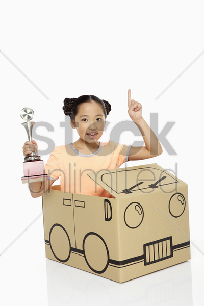girl holding a trophy and showing hand gesture stock photo