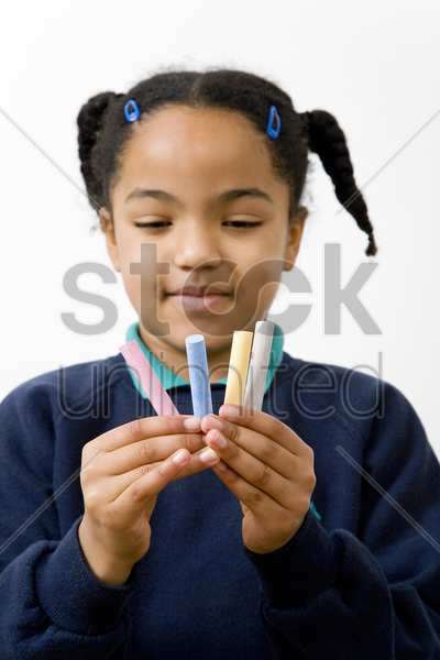 girl holding chalks of different colour stock photo