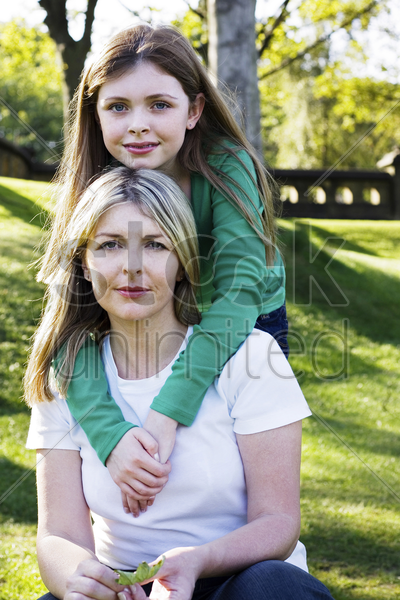 girl hugging her mother from the back stock photo