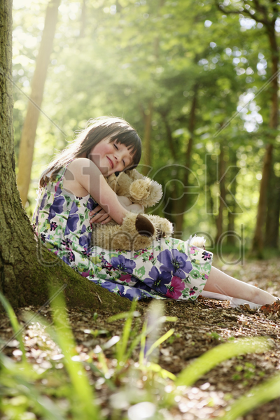 girl hugging her teddy bear stock photo