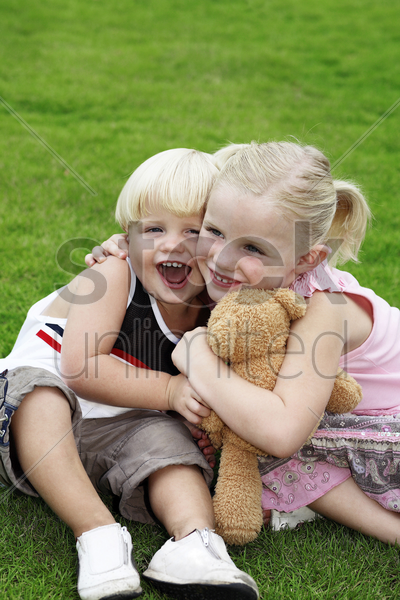 girl hugging little boy and toy bear stock photo