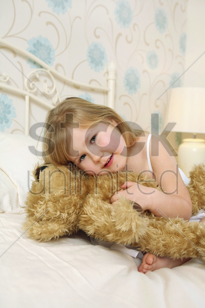 girl hugging teddy bear on bed stock photo