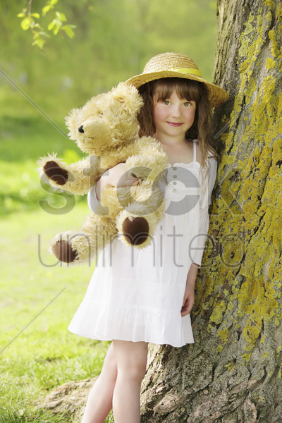girl hugging teddy bear stock photo