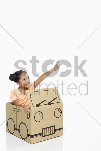 girl in cardboard bus showing hand gesture stock photo