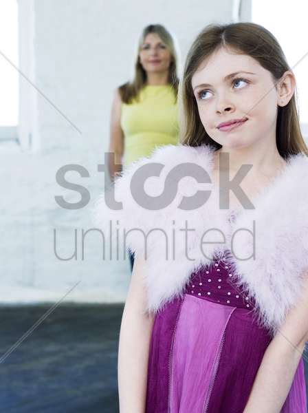 girl in lovely pink dress with her mother standing in the background stock photo