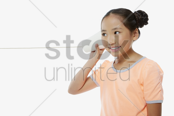 girl listening to a paper cup phone stock photo