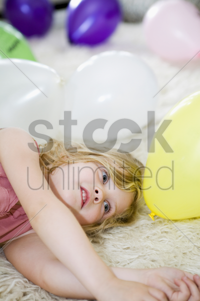 girl lying down with colourful balloons around her stock photo