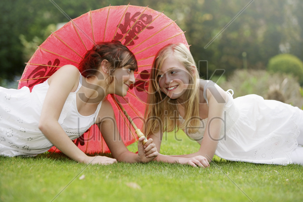 girl lying on the grass sharing an umbrella stock photo