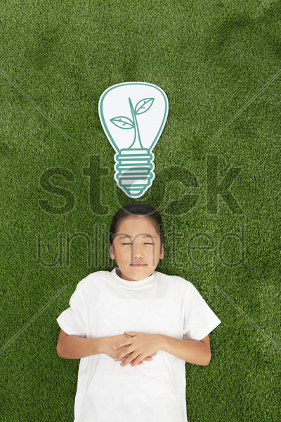 girl lying on the grass with eyes closed stock photo