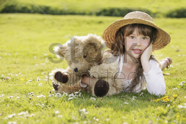 girl lying on the grass with her teddy bear stock photo